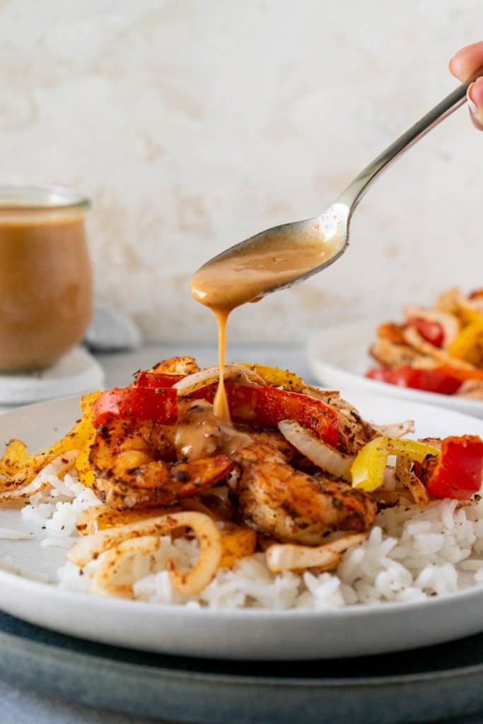 a spoon drizzling coconut curry sauce over shrimp and peppers