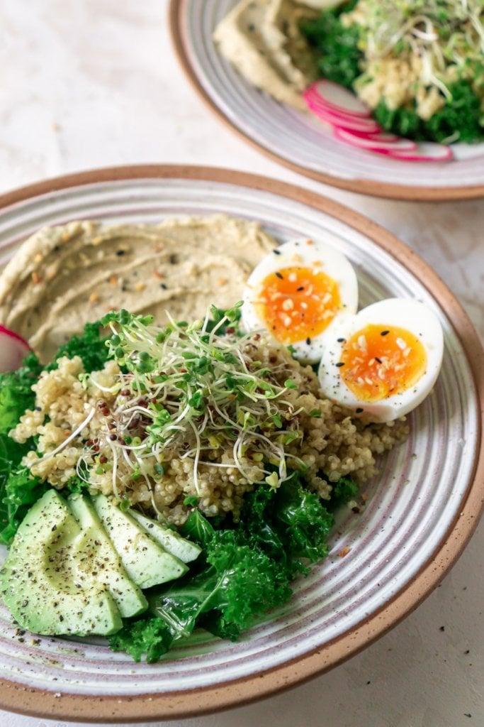 kale, quinoa, avocado, eggs, and hummus in a bowl