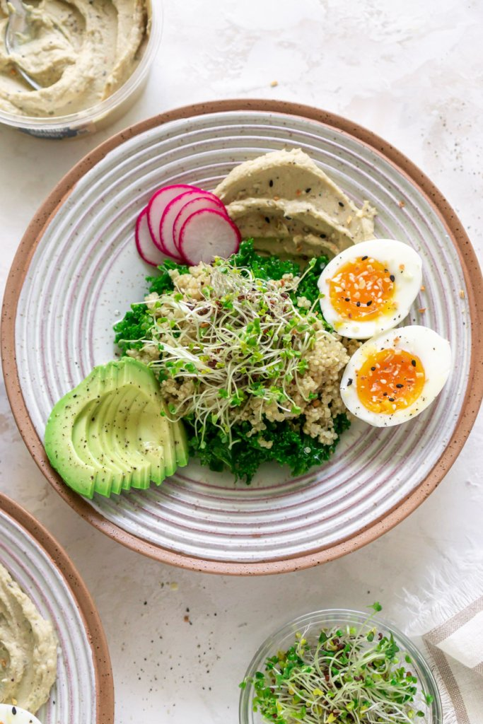 breakfast hummus bowl with eggs and avocado