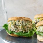 3 pineapple chicken salad croissant sandwiches on a grey plate