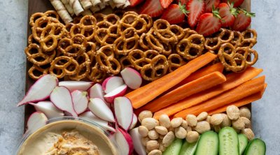 snack platter with hummus, strawberries, carrots, cucumbers, radishes, and pretzels